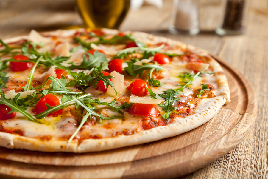 "Italian pizza ""Caprese"" lies on beautiful wooden table. At the top of a pizza cut baked cherry tomatoes arugula and Parmesan cheese slices. Nearby are the containers with spices and olive oil."